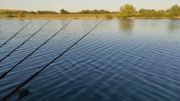 Calm blue river and four fishing rods